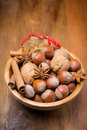 Assorted nuts and spices in a wooden bowl vertical close up Stock Image