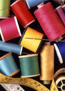 Assorted reels of cottons threads and sewing sundries cotton in close up needlecraft basket Royalty Free Stock Photo