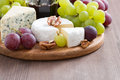 Assorted soft cheeses and fresh grapes on a wooden background close up Royalty Free Stock Images