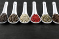 Assorted spices pepper and clove in white spoon on black wood Royalty Free Stock Photos