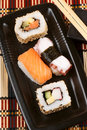 Assorted sushi japanese maki on a black tray with chopsticks ready to be eaten selective focus Stock Images