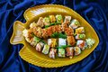 Assorted sushi rolls arranged in a yellow fish platter with blue scrunched fabric background Royalty Free Stock Photo