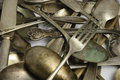 Assorted tarnished antique flatware on white patterns of silver brass silver plated from early s to post ww strewn about a black Royalty Free Stock Image