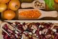 Assortment of beans, lentils, chickpea in wooden spoons on wood background