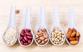 Assortment of beans and lentils in spoon on wooden background. a