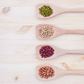 Assortment of beans and lentils in wooden spoon on wooden backgr