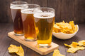 Assortment of beer glasses with nachos chips  on a wooden table Royalty Free Stock Photo