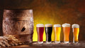 Assortment of beer glasses with a wooden barrel background dark yellow gradient Royalty Free Stock Photo
