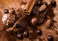Assortment chocolate with spices and candy cinnamon stick and crumbs and badiane on wooden table Royalty Free Stock Photos