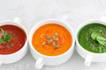 Assortment of colorful vegetable cream soup on white background a closeup top view Royalty Free Stock Images