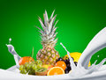 Assortment of exotic fruits splashing milk with fruit mix green background Stock Photography