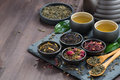 Assortment of fragrant dried teas and green tea on dark wooden table horizontal Stock Photography