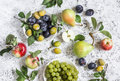 Assortment of fresh fruit grapes pears apples plums on a light background top view Stock Photography