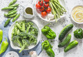 Assortment of fresh garden vegetables - asparagus, broccoli, beans, peppers, tomatoes, cucumbers, garlic, green peas on a light ba Royalty Free Stock Photo