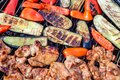 Assortment of fresh healthy colored vegetables, chicken meat grilled on BBQ grilling over a hot fire coals against green Royalty Free Stock Photo