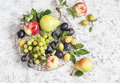 Assortment of fresh summer fruit grapes pears apples plums on a light background top view Stock Photo