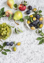 Assortment of fresh summer fruit grapes pears apples plums on a light background top view free space for text Stock Photography