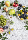 Assortment of fresh summer fruit grapes pears apples plums on a light background top view free space for text Stock Photo