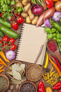 Assortment of fresh vegetables and blank recipe book on a wooden background Stock Photo