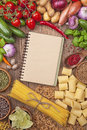 Assortment of fresh vegetables and blank recipe book on a wooden background Royalty Free Stock Photo