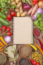 Assortment of fresh vegetables and blank recipe book on a wooden background Stock Image