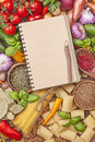 Assortment of fresh vegetables and blank recipe book on a wooden background Stock Images