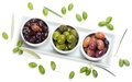 Assortment of olives colorful pickled in small individual dishes for snacks overhead top view on white Royalty Free Stock Photos