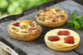 Assortment oof cheese tarts with tomato onion green pepper mushroom olive on a vintage table Stock Photo