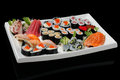 Assortment of rolls sushi and sashimi served on white plate Royalty Free Stock Photos