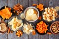 Assortment of salty snacks, top view table scene over wood Royalty Free Stock Photo