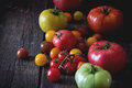 Assortment of tomatoes big raf red and green and cherry red yellow and orange over old wooden table dark rustic style day light Royalty Free Stock Photography