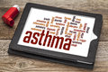 Asthma word cloud on a digital tablet screen with an inhaler Stock Photos