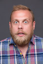 Astonished bearded man profile of on dark grey very surprised short haired blond in plaid shirt bugging his eyes Royalty Free Stock Photos