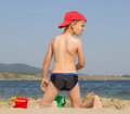 Astonished boy on the beach staring with his back playing and at something to camera Royalty Free Stock Photo