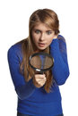 Astonished girl looking magnifying glass downwards over white background Royalty Free Stock Photos