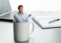 Astonished man in cup on the background of desktop Stock Photo