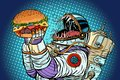 Astronaut monster eats burger. Greed and hunger of mankind conce Royalty Free Stock Photo