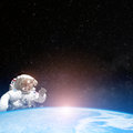 Astronaut in outer space behind the planet earth Royalty Free Stock Photo