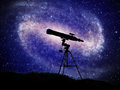 Astronomy a telescope with a large spiral galaxy in the background Stock Image