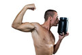 Athlete flexing muscles while kissing nutritional supplement container shirtless against white baackground Stock Photography