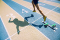 Athlete in gold shoes sprinting across starting line from the blocks over the of a race on a blue and tan running track Royalty Free Stock Photography
