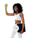 Athlete holding green apple and weighing machine Stock Photos