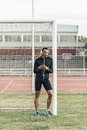 Athlete leaned on the goalpost listening to music stadium Royalty Free Stock Image