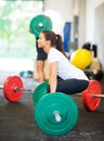 Athlete lifting barbell at healthclub side view of female Royalty Free Stock Images