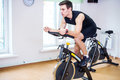 Athlete man biking in the gym, exercising his legs doing cardio training cycling bikes Royalty Free Stock Photo