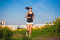 Athlete on morning jog in the sunflower s field cute Stock Photo