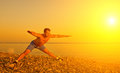 Athlete practicing yoga on beach at suns man playing sports and the sunset Stock Photos