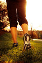 Athlete runner feet running on grass closeup shoe woman fitness sunrise jog workout wellness concept Stock Image
