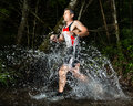 An athlete is running through a streambed Stock Photography