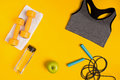 Athlete`s set with female clothing, dumbbells and bottle of water on yellow background Royalty Free Stock Photo